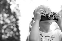 Little girl taking picture using vintage film camera Royalty Free Stock Photos