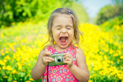 Little girl taking pictures on a meadow Stock Images