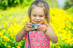 Little girl taking pictures on a meadow Royalty Free Stock Image
