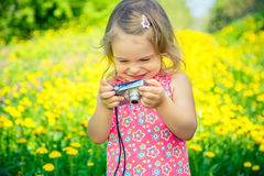 Little girl taking pictures on a meadow Stock Photos