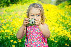 Little girl taking pictures on a meadow Stock Photography