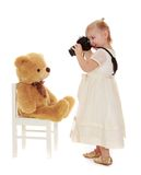 Little girl taking pictures of a Teddy bear Stock Photos
