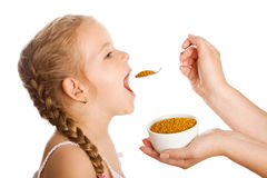 Little girl taking pollen - traditional remedies Royalty Free Stock Images