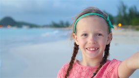 Happy little girl taking selfie at tropical beach on exotic island during summer vacation. Little girl taking selfie at tropical beach on exotic island during stock video