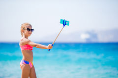 Little girl taking selfportrait by her smartphone on the beach. Kid enjoying her suumer vacation and making photos for Royalty Free Stock Images