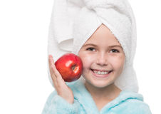 Little girl after taking a shower holding red apple beside her c. Portrait of cheerful little girl after taking a shower holding red apple beside her cheek Royalty Free Stock Photo