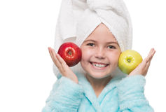 Little girl after taking a shower holding red and green apples b. Portrait of cheerful little girl after taking a shower holding red and green apples beside her Royalty Free Stock Image