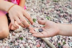 Little girl taking stones from friends hand. Concept of trust Royalty Free Stock Image