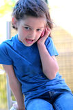 Little girl talking on the cell phone. A cute little 6 year old girl wearing jeans and a tee shirt talking on a cell phone, Shallow depth of field Stock Photo