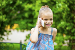 Little girl talking on cell phone against green of Park in summe Stock Photos
