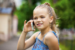 Little girl talking on cell phone against green of Park in summe Stock Photo