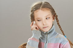 Little girl talking on cell phone. Beautiful little girl in sweater talking on cell phone, on gray background Royalty Free Stock Photography
