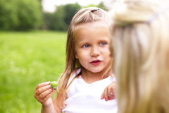 A little girl is talking with her mother stock photos