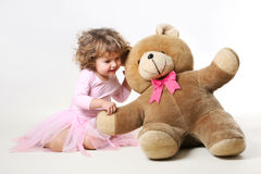 little girl is talking with her teddy