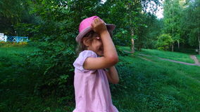 Little girl talking on a mobile phone. She moves through the park. Park with big trees and a pond. stock video footage