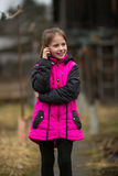 Little girl talking on mobile standing in the street. Royalty Free Stock Images