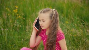 Little girl talking on the phone. On a background of green grass stock video
