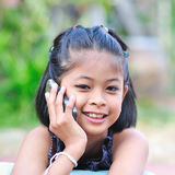 Little girl talking on the phone. Little girl talking on the phone,looking at camera royalty free stock image