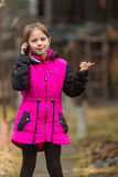 Little girl talking on phone standing in the yard. Happy. Royalty Free Stock Images
