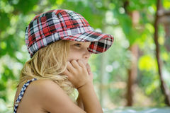 Little girl talking in plaid cap Stock Images