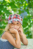 Little girl talking in plaid cap. Against green of the Park in summer Stock Photography