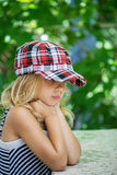 Little girl talking in plaid cap Stock Image