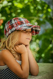 Little girl talking in plaid cap Royalty Free Stock Image