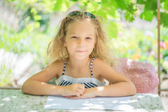Little girl talking Silit at table Royalty Free Stock Image