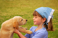 Little girl talking to puppy stock photography