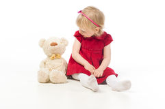 Little girl talking with toy bear Stock Images
