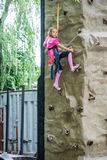 Little girl talking trains on climbing wall Royalty Free Stock Photos