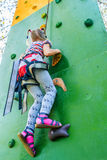 Little girl talking trains on climbing wall Stock Photo