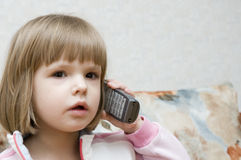 Little girl talks by phone Royalty Free Stock Photo