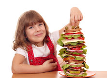 Little girl with tall sandwich Royalty Free Stock Photo