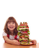 Little girl with tall sandwich on table Royalty Free Stock Photo