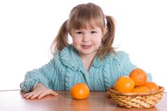 The little girl with tangerines Royalty Free Stock Photography