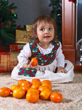Little girl with tangerines in the room with Christmas decoratio Stock Images