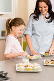 Little girl taste sprinkles cupcakes with mum Stock Images