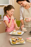 Little girl taste sprinkles decorating cupcake Stock Photo
