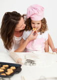 Little girl tasting a biscuit with her mother Stock Photo