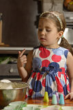 Little girl tasting the mixture for muffins Stock Photography