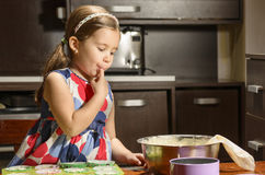 Little girl tasting the mixture for muffins Royalty Free Stock Image