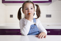 Little girl tasting a raw colorful cherry tomato. E Stock Images