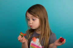 Little girl tasting a strawberry Stock Photos