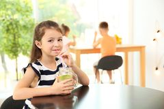 Little girl with natural lemonade at table indoors Stock Photography