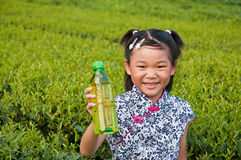 The little girl in the tea garden. The little girl with green tea Royalty Free Stock Images
