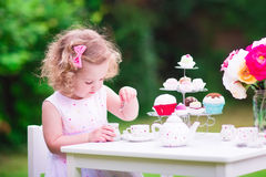 Little girl at tea party. Adorable funny toddler girl with curly hair wearing a colorful dress on her birthday playing tea party with a teddy bear doll, toy Stock Photography