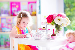Little girl at tea party. Adorable toddler girl with curly hair wearing a colorful dress on her birthday playing tea party with a doll, toy dishes, cup cakes and Royalty Free Stock Photography