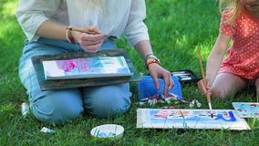 Little Girl and Teacher Drawing Together Outdoors stock video