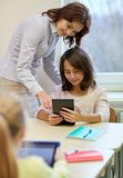 Little girl with teacher and tablet pc at school Royalty Free Stock Photo